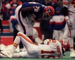 ORCHARD PARK, UNITED STATES: NY, UNITED STATES: Buffalo Bills Bruce Smith leans over Kansas City Chiefs Joe Montana (19) 23 Jan during the AFC championship game. Smith caused Montana a consussion forcing him to leave the game in the third quarter. The Bills defeated the Chiefs 30-13. (Photo credit should read DON EMMERT/AFP/Getty Images)